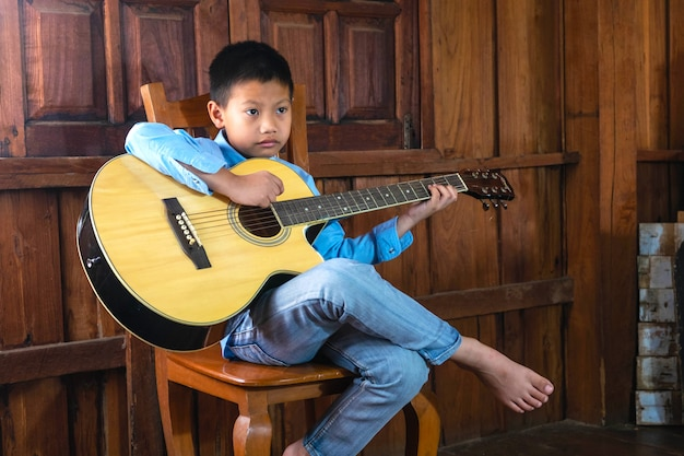 The boy is playing music with his favorite guitar. Premium Photo