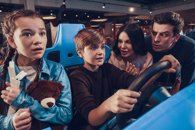 Boy is riding car in arcade. family is cheering. Premium Photo