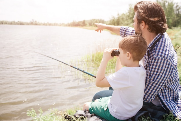 Boy is sitting with his dad at the river shore and looking through binoculars. adult man is pointing forward and holding fish-rod in right hand. Premium Photo