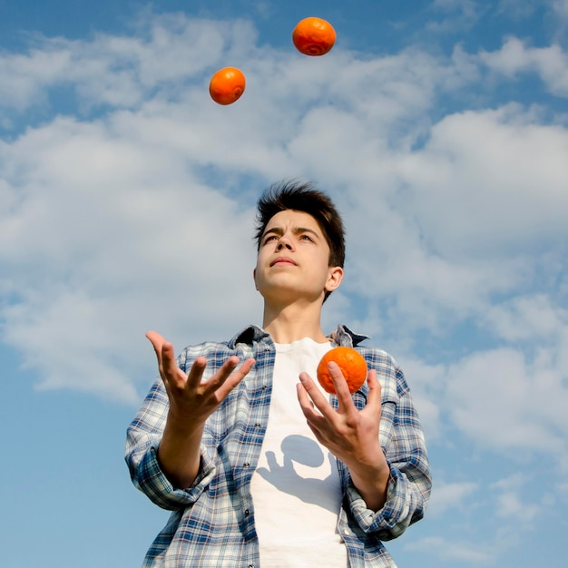 Boy juggles with oranges outdoors Free Photo