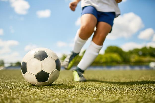 Boy kicking ball Premium Photo