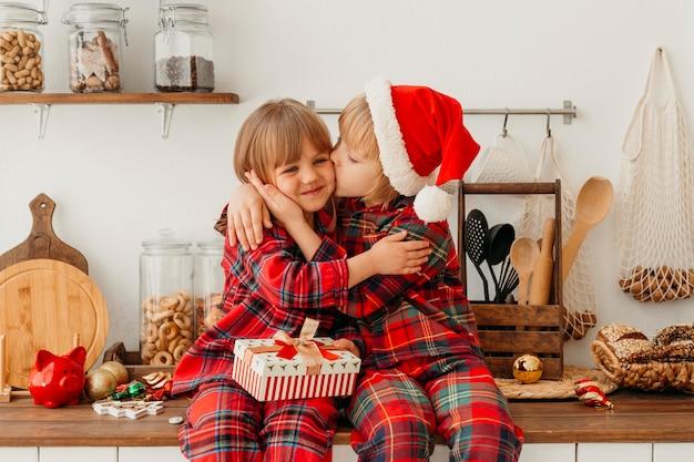 Мальчик целует в щеку свою сестру Premium Фотографии