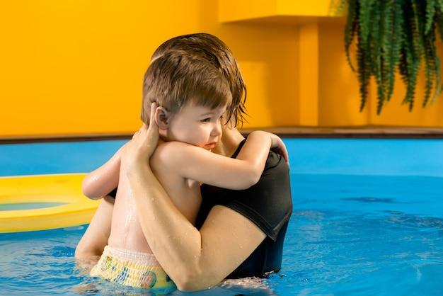 Мальчик учится плавать в бассейне с тренером Premium Фотографии