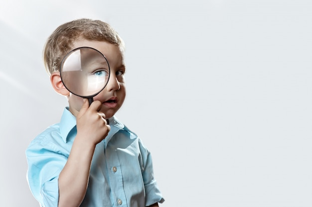 Boy in a light t-shirt looking into a large magnifying glass Premium Photo