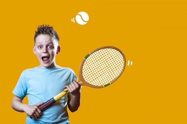 A boy in a light t-shirt with a tennis racket and a ball on orange Premium Photo