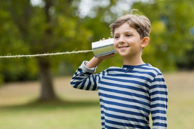 Boy listening through tin can phone Premium Photo