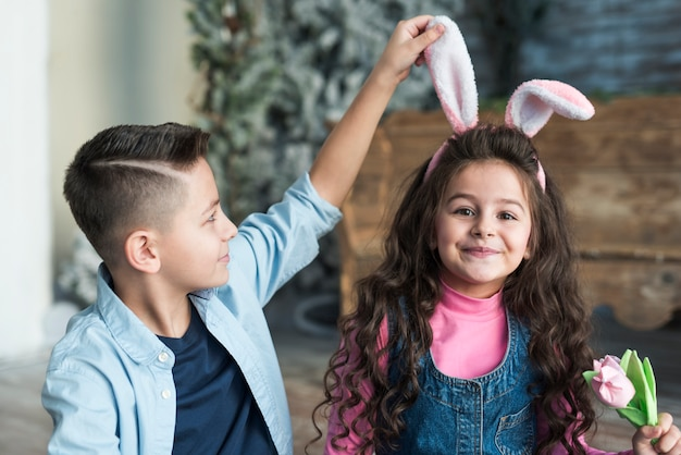 Boy looking at girl in bunny ears with tulip Free Photo