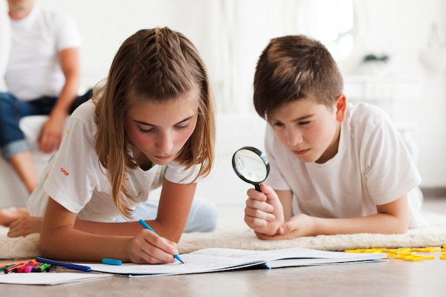 Boy looking through magnifying glass during his sister drawing on book Free Photo