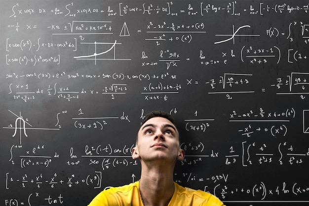 Boy looks apprehensively at a mathematical formula Premium Photo