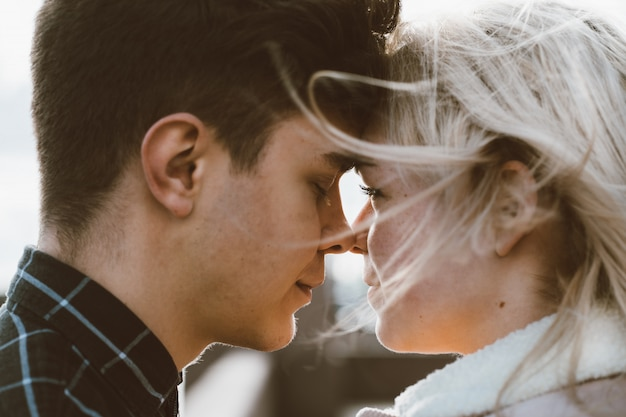 The boy looks tenderly at girl and wants to kiss. a young couple stands embracing Premium Photo