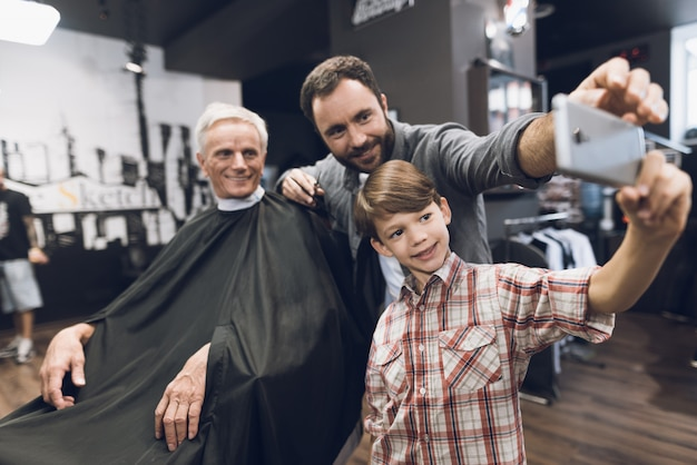 Boy make selfie with barber in barbershop Premium Photo
