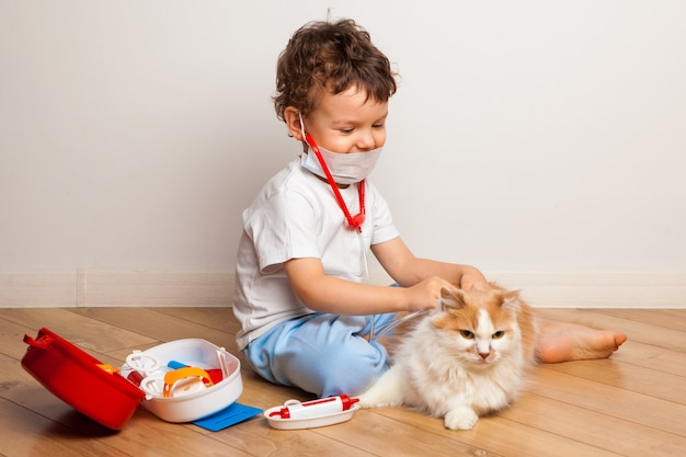 A boy in a medical mask with a stethoscope plays with a disgruntled cat in the hospital. Premium Photo