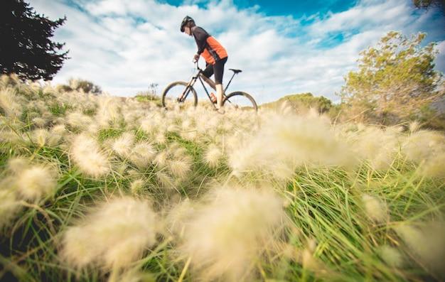 Boy on mountain bike pedaling through meadow Premium Photo