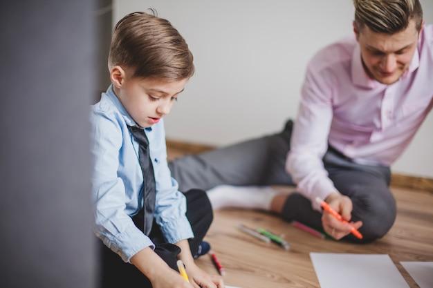 Мальчик рядом с отцом, сидящим на полу Бесплатные Фотографии