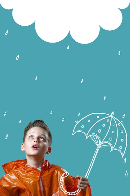 Boy in an orange raincoat and with a painted umbrella stands in the rain Premium Photo