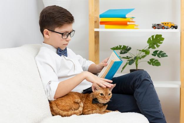 Gatto e lettura di coccole del ragazzo Foto Gratuite