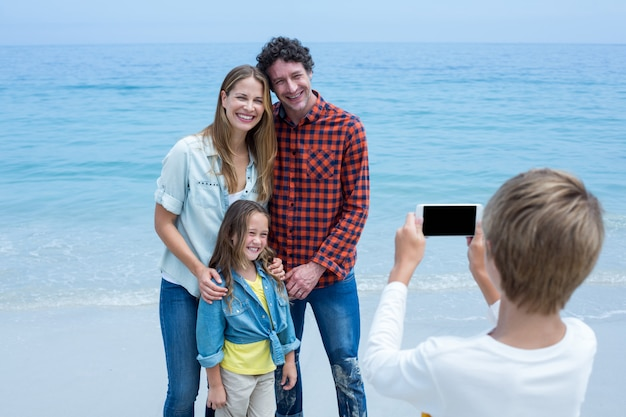 Boy photographing happy family at sea shore Premium Photo
