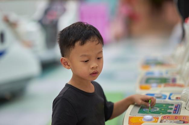 Boy play game in arcade alone Premium Photo