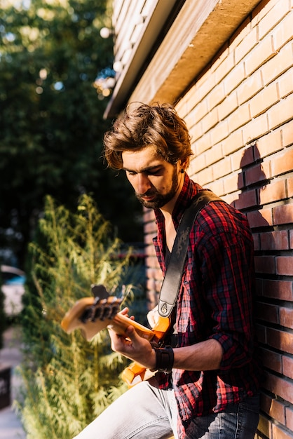 Boy playing the electric guitar standing on brick wall Free Photo