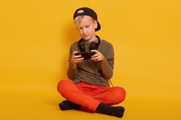 Мальчик играя игру через сотовый телефон, прелестное мужское усаживание ребенк изолированное на желтом цвете и держащ чернь, парень одевает вскользь, представляя с наушниками вокруг шеи, держа ноги пересеченные. Бесплатные Фотографии