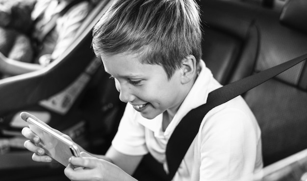 Boy playing on a smartphone in the car Free Photo
