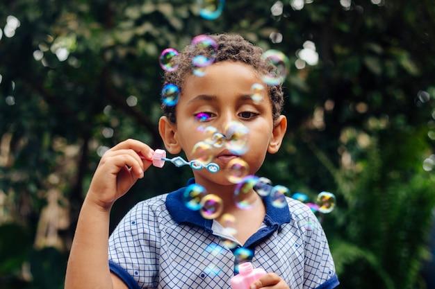 Мальчик играет мыльный пузырь Premium Фотографии