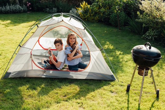 Boy playing ukulele sitting back to back his sister in tent near barbecue grill Free Photo