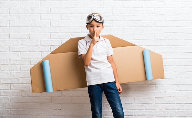 Boy playing with cardboard airplane wings on his back showing a sign of closing mouth Premium Photo