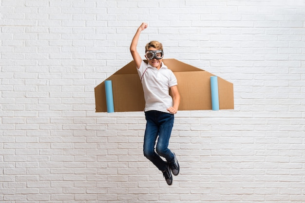 Boy playing with cardboard airplane wings jumping Premium Photo