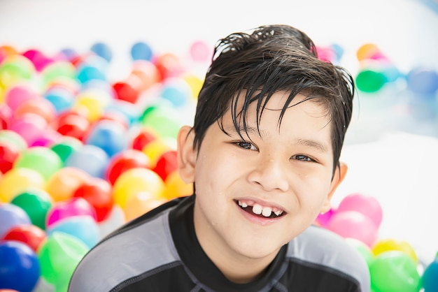 Boy playing with colourful ball in small swimming pool toy Free Photo