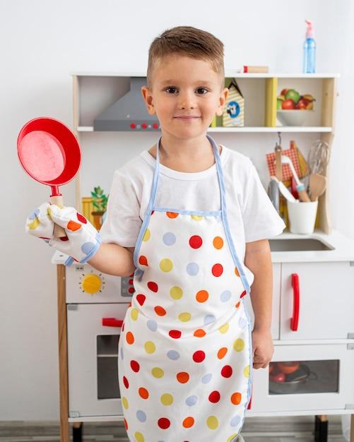 Ragazzo che gioca con un gioco di cucina al chiuso Foto Gratuite