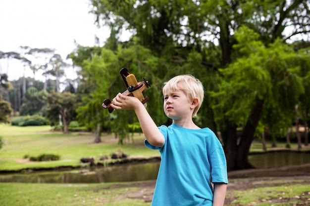 Boy playing with a toy aeroplane Premium Photo