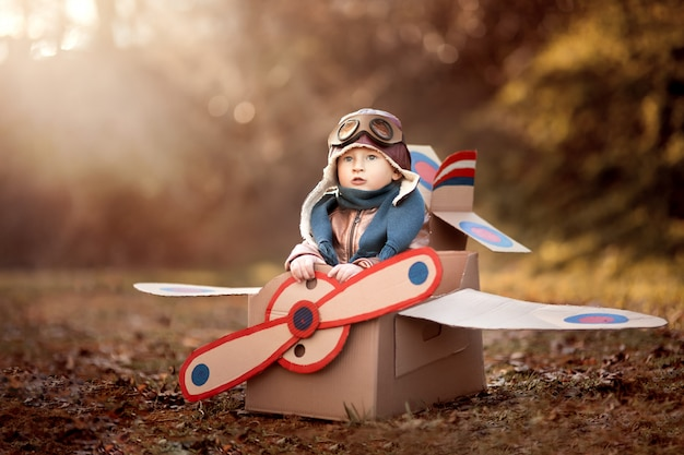 The boy plays in an airplane made of cardboard box and dreams of becoming a pilot Premium Photo