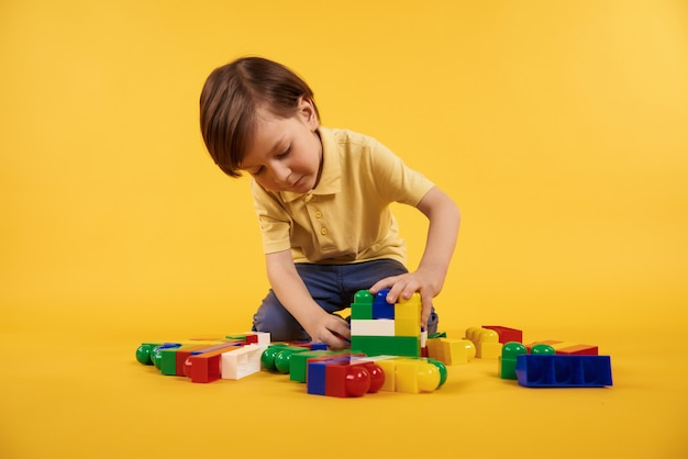 Boy plays with plastic toy bricks. children leisure concept. Premium Photo