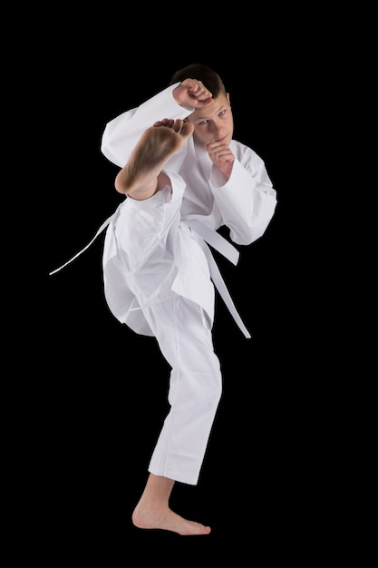 Boy posing with karate techniques in studio on black isolated Premium Photo