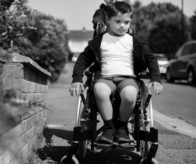 Мальчик толкает своего брата в инвалидной коляске Premium Фотографии