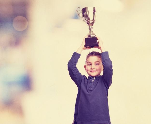 Boy raising his trophy Free Photo