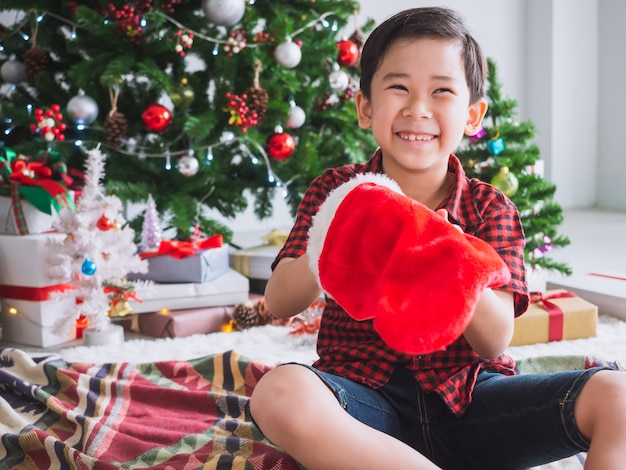 Boy in a red shirt is holding red sock and happy with funny to celebrate christmas with christmas tree Premium Photo