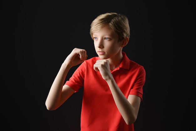 A boy in a red t-shirt with a short haircut on a black background holds his hands like in boxing, a protective pose Free Photo