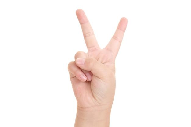勝利の兆候と白い背景で隔離の平和のクローズアップを示す少年の手。 Premium写真