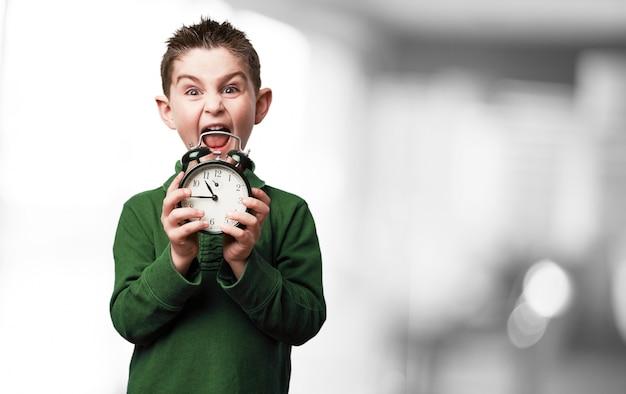 Boy screaming with an alarm clock Free Photo