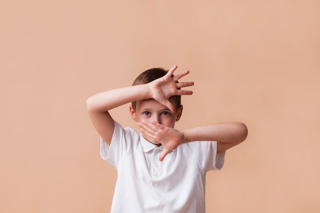 Boy showing stop gesture looking at camera on beige background Free Photo