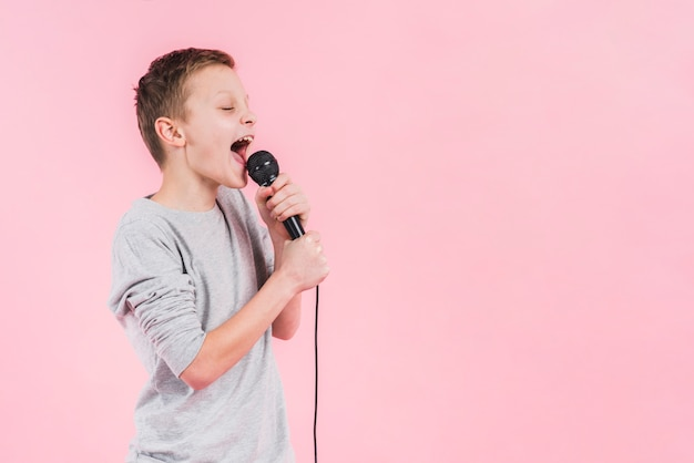 A boy singing song on microphone standing against pink backdrop Free Photo