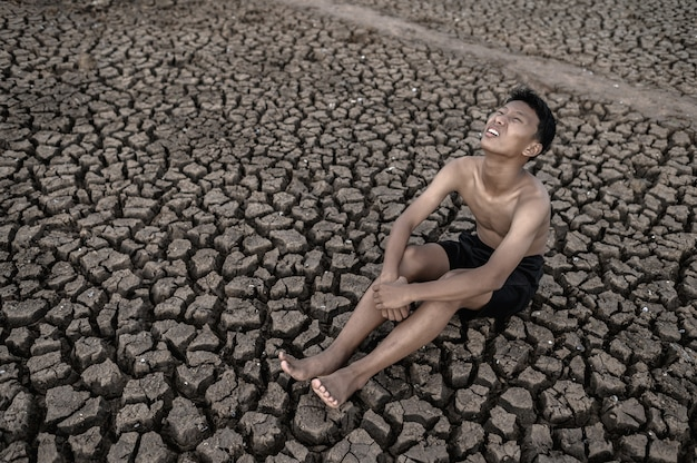 The boy sit hugging their knees bent and looking at the sky to ask for rain on dry soil. Free Photo