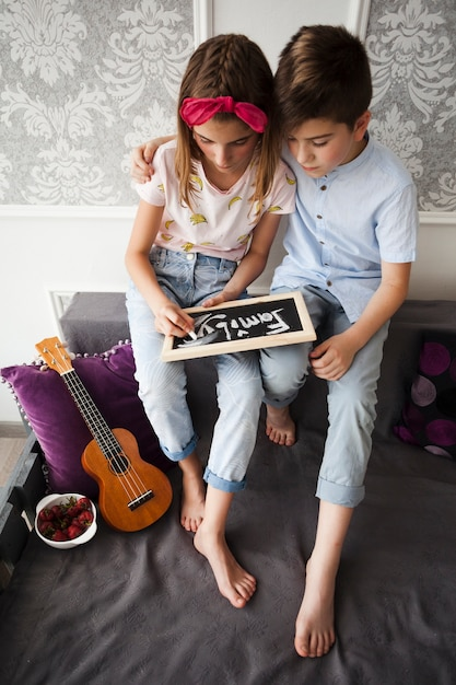 Boy siting with his sister writing family text on slate at home Free Photo
