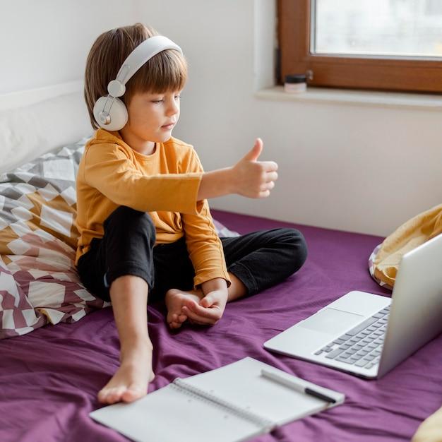Ragazzo seduto a letto e imparare i pollici in su Foto Gratuite