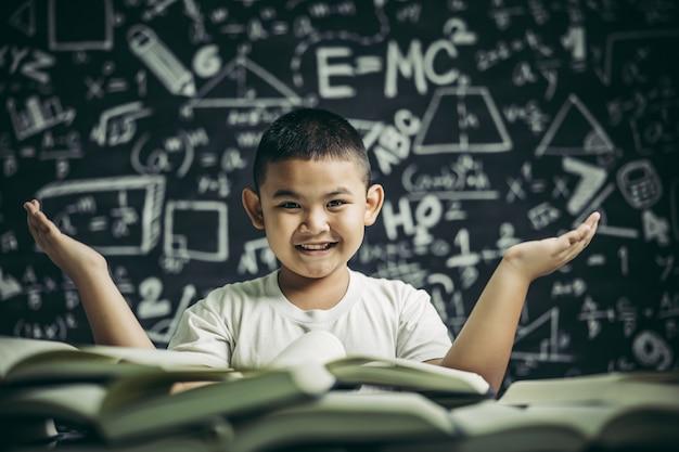 Un ragazzo seduto in classe a leggere un libro Foto Gratuite