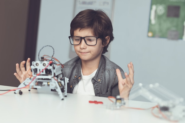 Boy sitting at desk and constructing robot at home Premium Photo