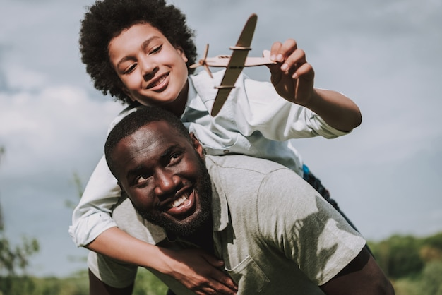 Boy sitting on father back and play with plane. Premium Photo