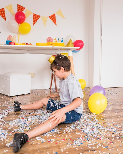 Boy sitting on floor playing with paper confetti after party celebration Free Photo